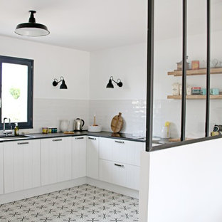 Inspiration for a mid-sized industrial u-shaped open plan kitchen with an integrated sink, louvered cabinets, white cabinets, quartz benchtops, white splashback, stainless steel appliances, cement tiles, no island, grey floor, ceramic splashback and black benchtop.