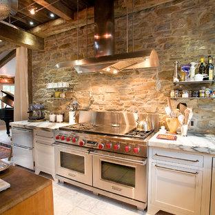 フィラデルフィアの巨大なインダストリアルスタイルのおしゃれなキッチン (シルバーの調理設備の、大理石カウンター、エプロンフロントシンク、シェーカースタイル扉のキャビネット、白いキャビネット) の写真
