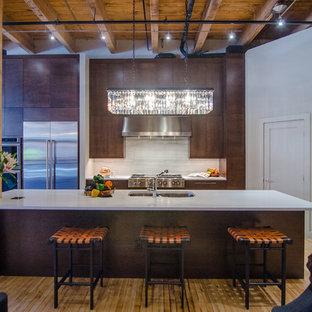 Offene Industrial Küche mit Unterbauwaschbecken, flächenbündigen Schrankfronten, dunklen Holzschränken, Küchenrückwand in Weiß, Rückwand aus Stein, Küchengeräten aus Edelstahl, braunem Holzboden und Kücheninsel in Denver