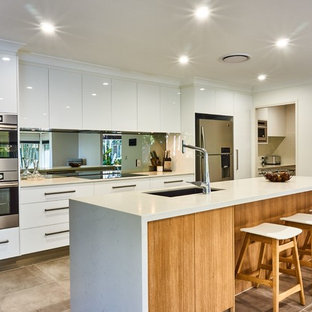 Photo of a mid-sized contemporary galley open plan kitchen in Gold Coast - Tweed with an undermount sink, flat-panel cabinets, white cabinets, mirror splashback, stainless steel appliances, with island, beige floor, white benchtop, quartz benchtops and metallic splashback.