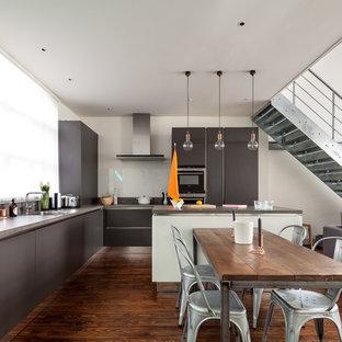 ロンドンのインダストリアルスタイルのおしゃれなキッチン (アンダーカウンターシンク、フラットパネル扉のキャビネット、グレーのキャビネット、コンクリートカウンター、白いキッチンパネル、ガラス板のキッチンパネル、パネルと同色の調理設備、無垢フローリング) の写真