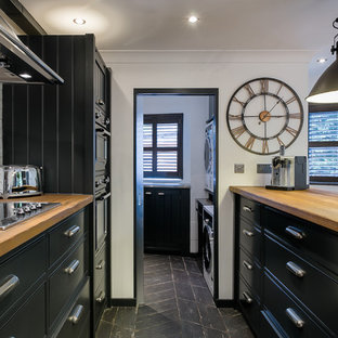 Inspiration for an industrial galley kitchen in London with flat-panel cabinets, black cabinets, wood worktops, white splashback, integrated appliances, an island, black floors and brown worktops.
