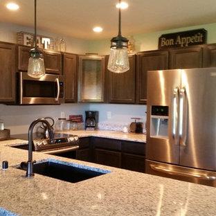 ミルウォーキーの小さいインダストリアルスタイルのおしゃれなキッチン (アンダーカウンターシンク、シェーカースタイル扉のキャビネット、黒いキャビネット、御影石カウンター、白いキッチンパネル、サブウェイタイルのキッチンパネル、シルバーの調理設備、クッションフロア) の写真