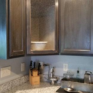 ミルウォーキーの小さいインダストリアルスタイルのおしゃれなキッチン (アンダーカウンターシンク、シェーカースタイル扉のキャビネット、黒いキャビネット、御影石カウンター、白いキッチンパネル、サブウェイタイルのキッチンパネル、シルバーの調理設備の、クッションフロア) の写真