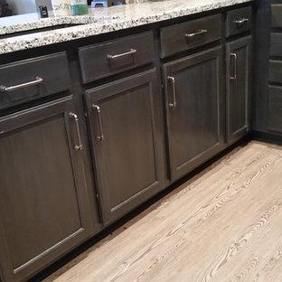 ミルウォーキーの小さいインダストリアルスタイルのおしゃれなキッチン (アンダーカウンターシンク、シェーカースタイル扉のキャビネット、ヴィンテージ仕上げキャビネット、御影石カウンター、シルバーの調理設備、クッションフロア) の写真