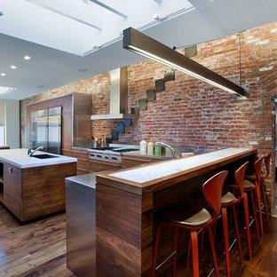 Geräumige Industrial Wohnküche in U-Form mit Unterbauwaschbecken, flächenbündigen Schrankfronten, dunklen Holzschränken, Edelstahl-Arbeitsplatte, Küchengeräten aus Edelstahl, dunklem Holzboden, zwei Kücheninseln und Küchenrückwand in Rot in New York