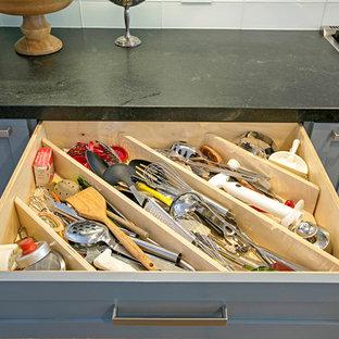 Idéer för att renovera ett stort industriellt kök, med en enkel diskho, släta luckor, skåp i ljust trä, vitt stänkskydd, stänkskydd i glaskakel, rostfria vitvaror, mellanmörkt trägolv och en köksö