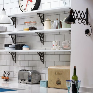 Design ideas for a small industrial l-shaped separate kitchen in Other with a double-bowl sink, flat-panel cabinets, blue cabinets, quartz benchtops, white splashback, subway tile splashback, black appliances, linoleum floors and a peninsula.