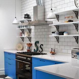 Inspiration för små, avskilda industriella l-kök, med blå skåp, vitt stänkskydd, stänkskydd i tunnelbanekakel, svarta vitvaror, en halv köksö, flerfärgat golv, en dubbel diskho, släta luckor, bänkskiva i kvarts och linoleumgolv
