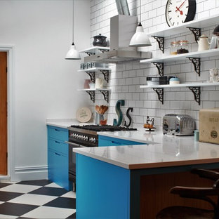 Design ideas for a small urban l-shaped enclosed kitchen in Other with a double-bowl sink, flat-panel cabinets, blue cabinets, engineered stone countertops, white splashback, metro tiled splashback, black appliances, lino flooring and a breakfast bar.