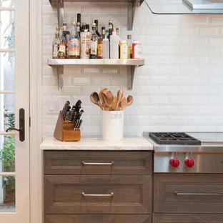 セントルイスの巨大なインダストリアルスタイルのおしゃれなキッチン (アンダーカウンターシンク、シェーカースタイル扉のキャビネット、濃色木目調キャビネット、クオーツストーンカウンター、白いキッチンパネル、サブウェイタイルのキッチンパネル、シルバーの調理設備の、淡色無垢フローリング) の写真