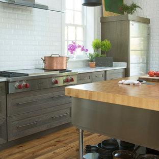 セントルイスの巨大なインダストリアルスタイルのおしゃれなキッチン (アンダーカウンターシンク、シェーカースタイル扉のキャビネット、濃色木目調キャビネット、クオーツストーンカウンター、白いキッチンパネル、サブウェイタイルのキッチンパネル、シルバーの調理設備、淡色無垢フローリング) の写真