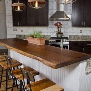 ニューヨークの中サイズのインダストリアルスタイルのおしゃれなキッチン (ダブルシンク、濃色木目調キャビネット、木材カウンター、白いキッチンパネル、サブウェイタイルのキッチンパネル、シルバーの調理設備の、シェーカースタイル扉のキャビネット、無垢フローリング) の写真