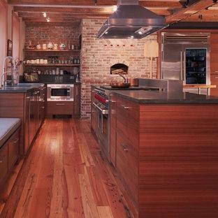 ボストンの広いインダストリアルスタイルのおしゃれなキッチン (アンダーカウンターシンク、フラットパネル扉のキャビネット、中間色木目調キャビネット、御影石カウンター、グレーのキッチンパネル、レンガのキッチンパネル、シルバーの調理設備、無垢フローリング、茶色い床) の写真