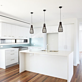 This is an example of a medium sized contemporary l-shaped kitchen/diner in Melbourne with a double-bowl sink, blue splashback, porcelain splashback, plywood flooring, an island and brown floors.