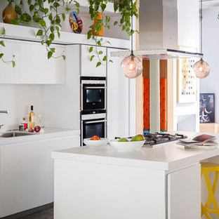 Photo of an eclectic galley open plan kitchen in London with a submerged sink, flat-panel cabinets, white cabinets, composite countertops, stainless steel appliances and an island.