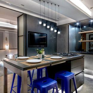 Modelo de cocina comedor urbana, pequeña, con armarios con paneles lisos, salpicadero metalizado, salpicadero con efecto espejo, suelo de cemento, una isla, puertas de armario en acero inoxidable y suelo gris