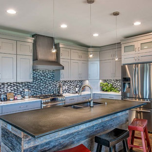 Inspiration for a mid-sized industrial l-shaped open plan kitchen in Other with a double-bowl sink, flat-panel cabinets, white cabinets, zinc benchtops, multi-coloured splashback, mosaic tile splashback, stainless steel appliances, medium hardwood floors and with island.