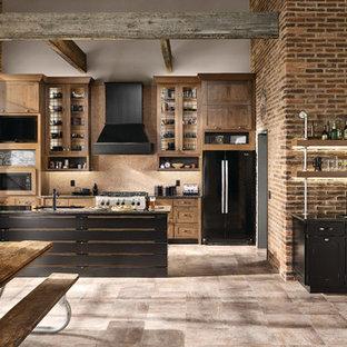 Inredning av ett industriellt stort kök, med en undermonterad diskho, skåp i shakerstil, skåp i slitet trä, granitbänkskiva, beige stänkskydd, stänkskydd i mosaik, svarta vitvaror, en halv köksö och beiget golv