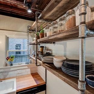 Kleine Industrial Wohnküche in U-Form mit Landhausspüle, Schrankfronten im Shaker-Stil, schwarzen Schränken, Arbeitsplatte aus Holz, Küchenrückwand in Weiß, Küchengeräten aus Edelstahl, hellem Holzboden, Halbinsel und Rückwand aus Metrofliesen in Chicago