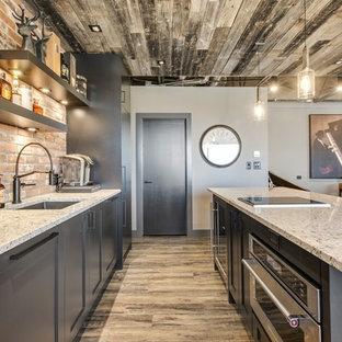 カルガリーの中サイズのインダストリアルスタイルのおしゃれなキッチン (アンダーカウンターシンク、シェーカースタイル扉のキャビネット、クオーツストーンカウンター、オレンジのキッチンパネル、レンガのキッチンパネル、パネルと同色の調理設備、クッションフロア、茶色い床、白いキッチンカウンター) の写真
