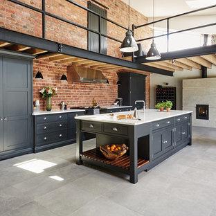 マンチェスターの大きいインダストリアルスタイルのおしゃれなキッチン (シェーカースタイル扉のキャビネット、黒いキャビネット、珪岩カウンター、パネルと同色の調理設備) の写真