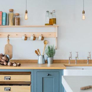 他の地域の中サイズのインダストリアルスタイルのおしゃれなキッチン (エプロンフロントシンク、シェーカースタイル扉のキャビネット、グレーのキャビネット、コンクリートカウンター、淡色無垢フローリング) の写真