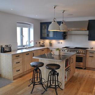 Medium sized urban u-shaped kitchen in Kent with beige cabinets, zinc worktops, stainless steel appliances, light hardwood flooring and a breakfast bar.
