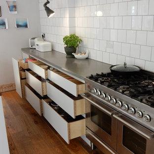 Idee per una piccola cucina industriale con ante lisce, ante grigie, top in cemento, paraspruzzi bianco, paraspruzzi con piastrelle in ceramica e elettrodomestici in acciaio inossidabile