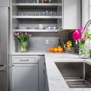 デトロイトの小さいインダストリアルスタイルのおしゃれなキッチン (アンダーカウンターシンク、シェーカースタイル扉のキャビネット、グレーのキャビネット、クオーツストーンカウンター、グレーのキッチンパネル、セラミックタイルのキッチンパネル、シルバーの調理設備、濃色無垢フローリング) の写真