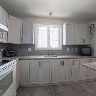 モントリオールのインダストリアルスタイルのおしゃれなキッチン (シングルシンク、シェーカースタイル扉のキャビネット、グレーのキャビネット、ラミネートカウンター、グレーのキッチンパネル、セラミックタイルのキッチンパネル、黒い調理設備、磁器タイルの床) の写真