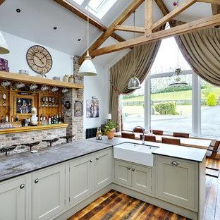 他の地域の広いラスティックスタイルのおしゃれなキッチン (シェーカースタイル扉のキャビネット、緑のキャビネット、木材のキッチンパネル、淡色無垢フローリング、ベージュの床、グレーのキッチンカウンター) の写真