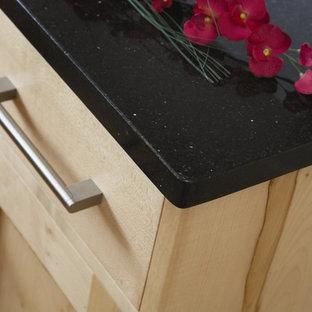 Modelo de cocina comedor contemporánea, pequeña, sin isla, con fregadero bajoencimera, armarios estilo shaker, puertas de armario de madera clara, encimera de granito, salpicadero metalizado, salpicadero de azulejos de cerámica, electrodomésticos negros y suelo de travertino