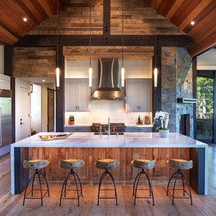 他の地域の大きいラスティックスタイルのおしゃれなキッチン (シェーカースタイル扉のキャビネット、グレーのキャビネット、大理石カウンター、白いキッチンパネル、モザイクタイルのキッチンパネル、シルバーの調理設備の、無垢フローリング、茶色い床、白いキッチンカウンター、エプロンフロントシンク) の写真