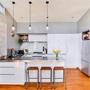 オークランドの大きいインダストリアルスタイルのおしゃれなキッチン (ダブルシンク、フラットパネル扉のキャビネット、白いキャビネット、ステンレスカウンター、白いキッチンパネル、ガラス板のキッチンパネル、シルバーの調理設備、無垢フローリング、マルチカラーの床) の写真