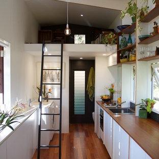 Ejemplo de cocina comedor lineal, actual, pequeña, con fregadero encastrado, puertas de armario blancas, encimera de madera y suelo de madera en tonos medios