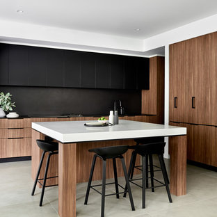 Inspiration for a contemporary l-shaped eat-in kitchen in Sydney with flat-panel cabinets, medium wood cabinets, black splashback, black appliances, with island, grey floor, black benchtop, a double-bowl sink and porcelain floors.