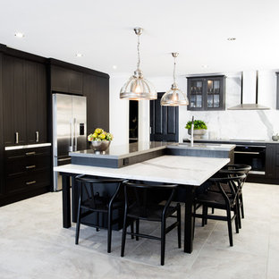Photo of a small transitional l-shaped eat-in kitchen in Central Coast with a double-bowl sink, black cabinets, quartz benchtops, white splashback, stone slab splashback, stainless steel appliances, ceramic floors, with island, grey floor, shaker cabinets and white benchtop.
