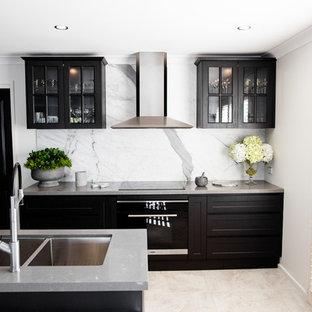 セントラルコーストの小さいモダンスタイルのおしゃれなキッチン (ダブルシンク、ガラス扉のキャビネット、黒いキャビネット、クオーツストーンカウンター、白いキッチンパネル、石スラブのキッチンパネル、シルバーの調理設備の、セラミックタイルの床、グレーの床) の写真