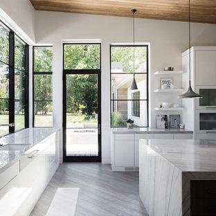 他の地域の中くらいのコンテンポラリースタイルのおしゃれなキッチン (アンダーカウンターシンク、フラットパネル扉のキャビネット、白いキャビネット、珪岩カウンター、パネルと同色の調理設備、グレーの床、クッションフロア) の写真