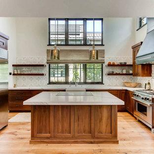 Modelo de cocina en U, clásica, con fregadero sobremueble, armarios estilo shaker, puertas de armario de madera oscura, electrodomésticos de acero inoxidable, suelo de madera en tonos medios, una isla y suelo marrón