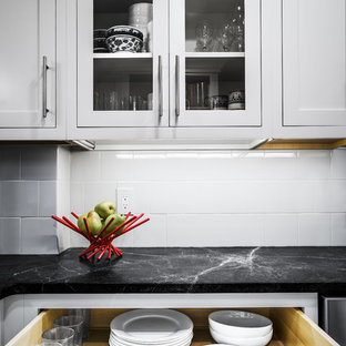 Small transitional u-shaped eat-in kitchen in Philadelphia with an undermount sink, beaded inset cabinets, white cabinets, soapstone benchtops, white splashback, glass tile splashback, stainless steel appliances, porcelain floors and a peninsula.