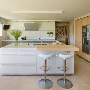 This is an example of a medium sized contemporary l-shaped kitchen/diner in Other with a double-bowl sink, flat-panel cabinets, white cabinets, composite countertops, white splashback, glass sheet splashback, stainless steel appliances, an island, beige floors and white worktops.