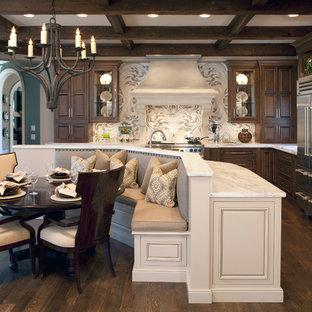 Ejemplo de cocina comedor en L, clásica, grande, con electrodomésticos de acero inoxidable, encimera de mármol, armarios con paneles con relieve, puertas de armario de madera en tonos medios, suelo de madera oscura, una isla y encimeras blancas