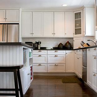 Amerikansk inredning av ett mellanstort svart svart kök, med skåp i shakerstil, vita skåp, granitbänkskiva, vitt stänkskydd, stänkskydd i tunnelbanekakel, rostfria vitvaror, mellanmörkt trägolv, en köksö och brunt golv