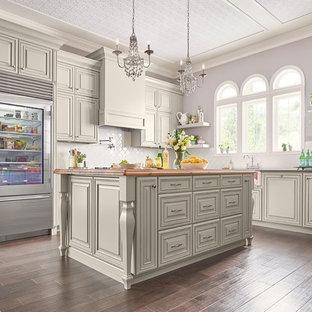 他の地域の大きいシャビーシック調のおしゃれなキッチン (エプロンフロントシンク、レイズドパネル扉のキャビネット、グレーのキャビネット、御影石カウンター、白いキッチンパネル、サブウェイタイルのキッチンパネル、シルバーの調理設備の、濃色無垢フローリング、茶色い床) の写真