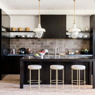 Ispirazione per una grande cucina minimal con paraspruzzi marrone, paraspruzzi con piastrelle in ceramica, ante lisce, ante in legno bruno, parquet chiaro, isola e elettrodomestici in acciaio inossidabile