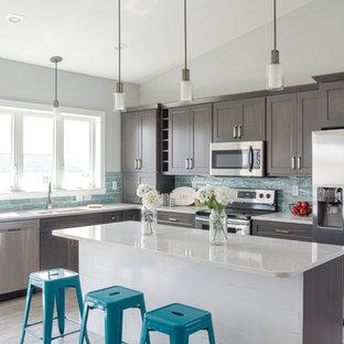他の地域の中サイズのシャビーシック調のおしゃれなキッチン (ダブルシンク、濃色木目調キャビネット、クオーツストーンカウンター、青いキッチンパネル、ガラスタイルのキッチンパネル、シルバーの調理設備の、淡色無垢フローリング、ベージュの床、シェーカースタイル扉のキャビネット) の写真