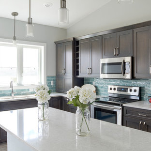Photo of a mid-sized shabby-chic style l-shaped eat-in kitchen in Other with a double-bowl sink, dark wood cabinets, quartz benchtops, blue splashback, glass tile splashback, stainless steel appliances, light hardwood floors, with island, beige floor and shaker cabinets.