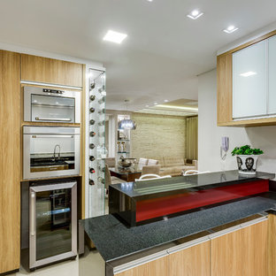 Photo of a mid-sized contemporary u-shaped open plan kitchen in Other with a double-bowl sink, flat-panel cabinets, light wood cabinets, granite benchtops, white splashback, ceramic splashback, stainless steel appliances, porcelain floors and a peninsula.